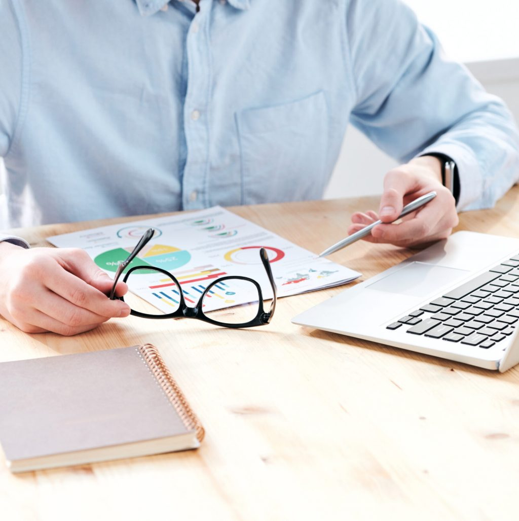Close-up of unrecognizable analyst sitting at desk and analyzing charts while planning marketing strategy